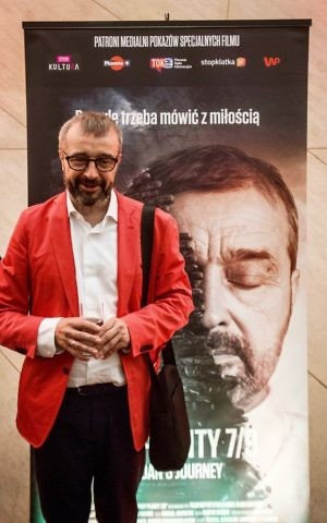 Bogdan Bialek in front of a movie poster for the documentary 'Bogdan's Journey.' (Courtesy)
