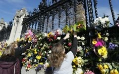 People place flowers outside Britain's parliament in London, Saturday March 25, 2017, for the victims of the Westminster terror attack. (AP Photo/Kirsty Wigglesworth)