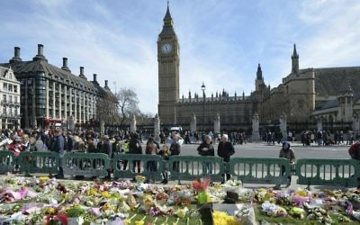People look at tributes in Parliament Square, London, Saturday, March 25, 2017, laid out for the victims of the Westminster attack on March 22, 2017. (John Stillwell/PA via AP)