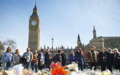 People look at floral tributes in Parliament Square, London, Sunday, March 26, 2017, laid out for the victims of the Westminster attack on Wednesday.  (Dominic Lipinski/PA via AP)