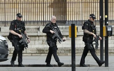 Armed police officers enter the Houses of Parliament in London, Wednesday, March 23, 2017 after the House of Commons sitting was suspended as witnesses reported sounds like gunfire outside. (AP Photo/Kirsty Wigglesworth)