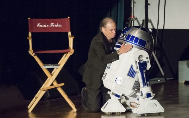 Todd Fisher hugs Star Wars character R2-D2 at the Carrie Fisher and Debbie Reynolds Memorial Service at The Forest Lawn on Saturday, March 25, 2017, in Los Angeles. Laughter, music and the tapping of dancing shoes reverberated throughout a public memorial to Debbie Reynolds and Carrie Fisher, which loved ones say is just how the actresses would have wanted it. Willy Sanjuan/Invision/AP)