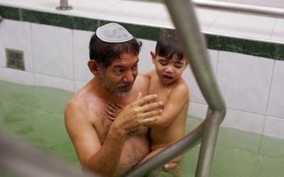 In this March 19, 2017 photo, Franklin Perez dips his son in a special bath to mark their conversion to Judaism in Bogota, Colombia.  (AP Photo/Christine Armario)
