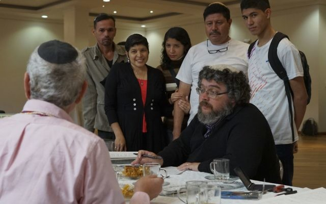 In this March 19, 2017 photo, a rabbi fills out paperwork in Bogota, Colombia, making the conversion of nine Venezuelans to Judaism official before their departure to Israel. (AP Photo/Christine Armario)