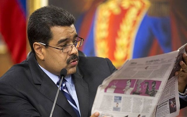 In this Tuesday, May 17, 2016 file photo, President Nicolas Maduro reads a newspaper during a news conference at Miraflores presidential palace in Caracas, Venezuela. (AP/Ariana Cubillos)