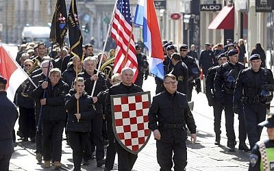 In this photo taken Sunday, Feb. 26, 2017, a group of right-wing radicals wave Croatian and US flags as they march through downtown Zagreb. (AP Photo)