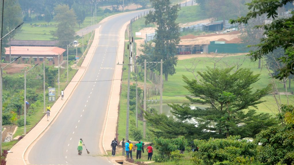 An empty street in the Rwandan capital of Kigali on February 25, 2017, as a woman sweeps during Umuganda community service time. (Melanie Lidman/Times of Israel)