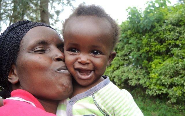 A woman goofs around with her neighbor's baby during the Umuganda community meeting in Kigali, Rwanda on February 25, 2017. (Melanie Lidman/Times of Israel)