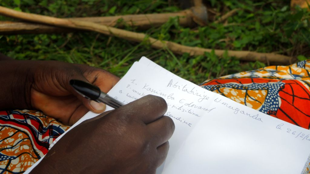 Residents of Kimana Village, a middle-class neighborhood in Kigali, Rwanda, sign in on the attendance sheet at the Umuganda community meeting on February 25, 2017. (Melanie Lidman/Times of Israel)