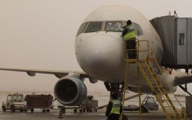 Illustrative: A maintenance worker cleans the windscreen of an airplane during a sandstorm at Ben Gurion International Airport on December 12, 2010. (Tsahi Ben-Ami/Flash 90)