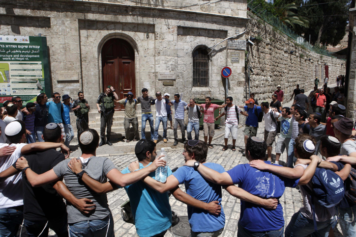 Israeli Border Police officers stand with Jewish settlers as they form a large circle and dance, outside the Austrian Hospice in the Old City of Jerusalem, during the Jewish holiday of Lag Ba'Omer on April 28, 2013. (Illustrative photo: Sliman Khader/FLASH90)