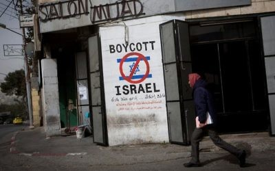 A Palestinian man walks past graffiti calling for a boycott of Israel on a street in the West Bank city of Bethlehem on February 11, 2015. (Miriam Alster/Flash 90)