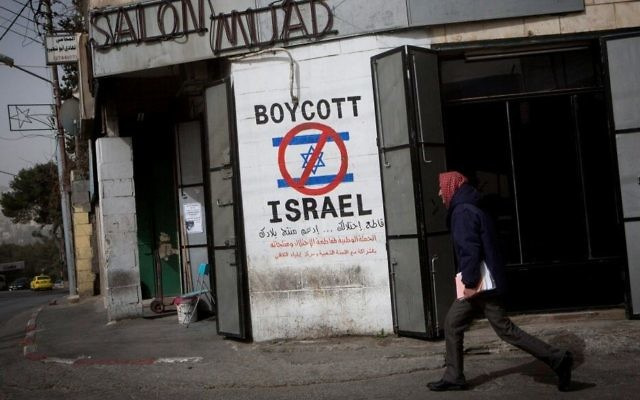 Illustrative: A Palestinian man walks past graffiti calling for a boycott of Israel on a street in the West Bank city of Bethlehem on February 11, 2015. (Miriam Alster/Flash 90)