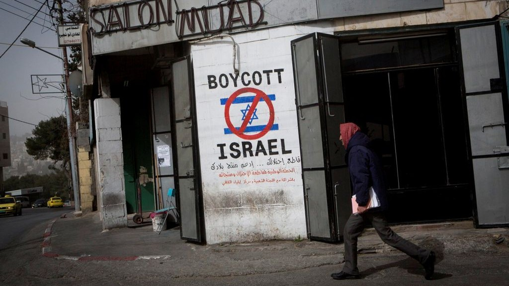 A Palestinian man walks pasy graffiti calling to boycott Israel on a street in the West Bank city of Bethlehem on February 11, 2015. (Miriam Alster/Flash 90)