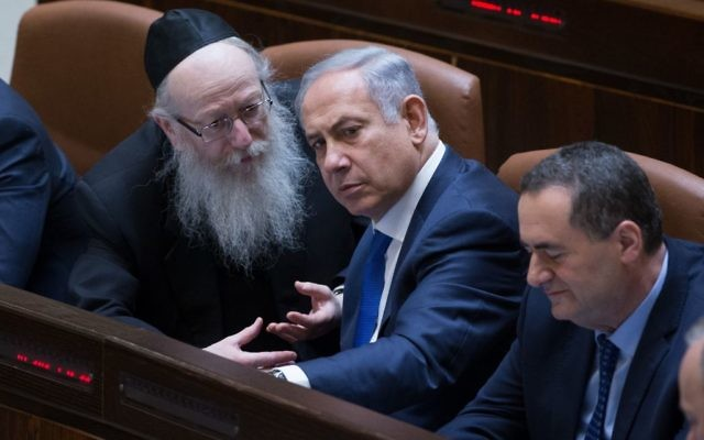 Prime Minister Benjamin Netanyahu (c) speaks with then-health minister Yaakov Litzman (l) at the Knesset on March 28, 2016. (Yonatan Sindel/Flash90)