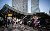 People wait for the bus near Hashalom train station by the Azrieli towers in Tel Aviv, September 22, 2016. (Miriam Alster/Flash90)