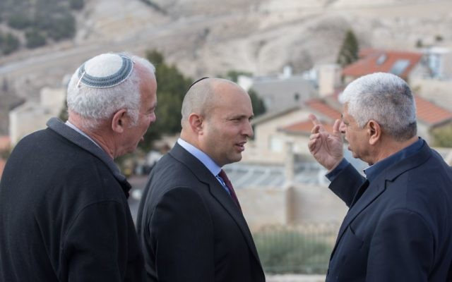 Jewish Home party chairman Naftali Bennett (C) speaks with Mayor of Ma'ale Adumim Benny Kasriel (R) before the start of a special party faction meeting in the Israeli settlement of Ma'ale Adumim, in the West Bank, on January 2, 2017. (Yonatan Sindel/Flash90)