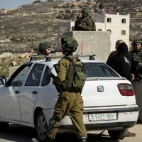 Illustrative. IDF soldiers check Palestinian cars at a checkpoint in the West Bank village of Yatta on February 10, 2017. (Wisam Hashlamoun/Flash90/File)
