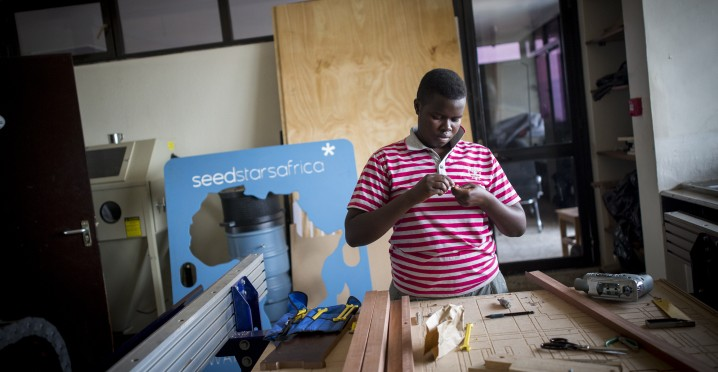 A young woman works with the laser printer in FabLab, a maker's space across the hall from K-Lab in Kigali, Rwanda on February 16, 2017. (Miriam Alster/Flash90)