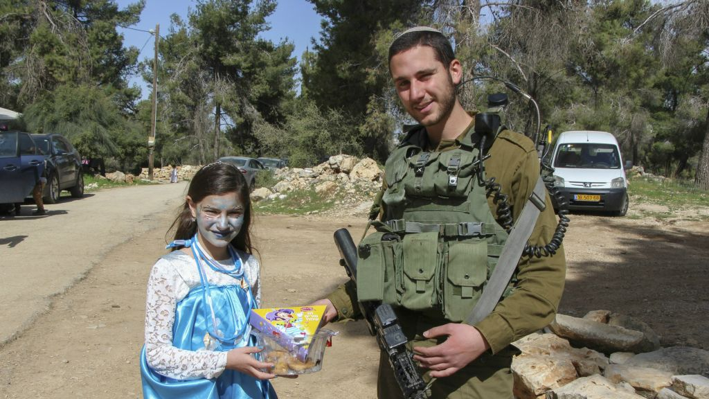 An Israeli soldier receives Mishloach manot from a girl in Shmurat Oz Vegaon in Gush Etzion, on March 12, 2017, during the Jewish holiday of Purim. (Gershon Elinson/Flash90)