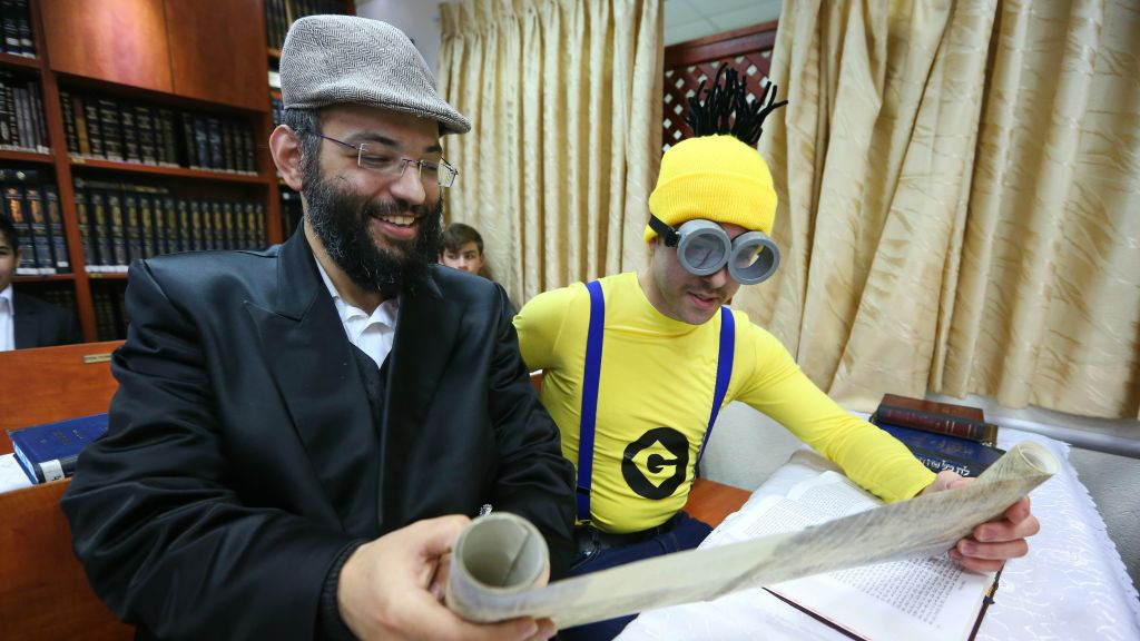 Ultra-Orthodox Jewish men read a Scroll of Esther, which tells the story of the Jewish festival of Purim, in Beit Shemesh, March 11, 2017. (Yaakov Lederman/Flash90)
