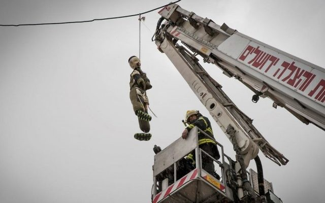 A firefighter takes down a large doll dressed as an ultra-Orthodox Jewish soldier hung in the ultra-Orthodox Jerusalem neighborhood of Mea Shearim, on March 13, 2017. (Nati Shohat/Flash90)