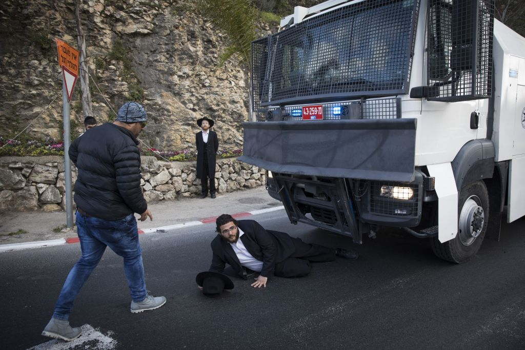 Ultra-Orthodox Jewish men protest against the arrest of a Jewish seminary student who failed to comply with a recruitment order, at the entrance to Jerusalem, on March 20, 2017. (Yonatan Sindel/Flash90)