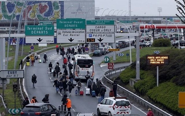 Travelers walk on the highway to the Orly airport, south of Paris, Saturday, March, 18, 2017. (AP Photo/Thibault Camus)