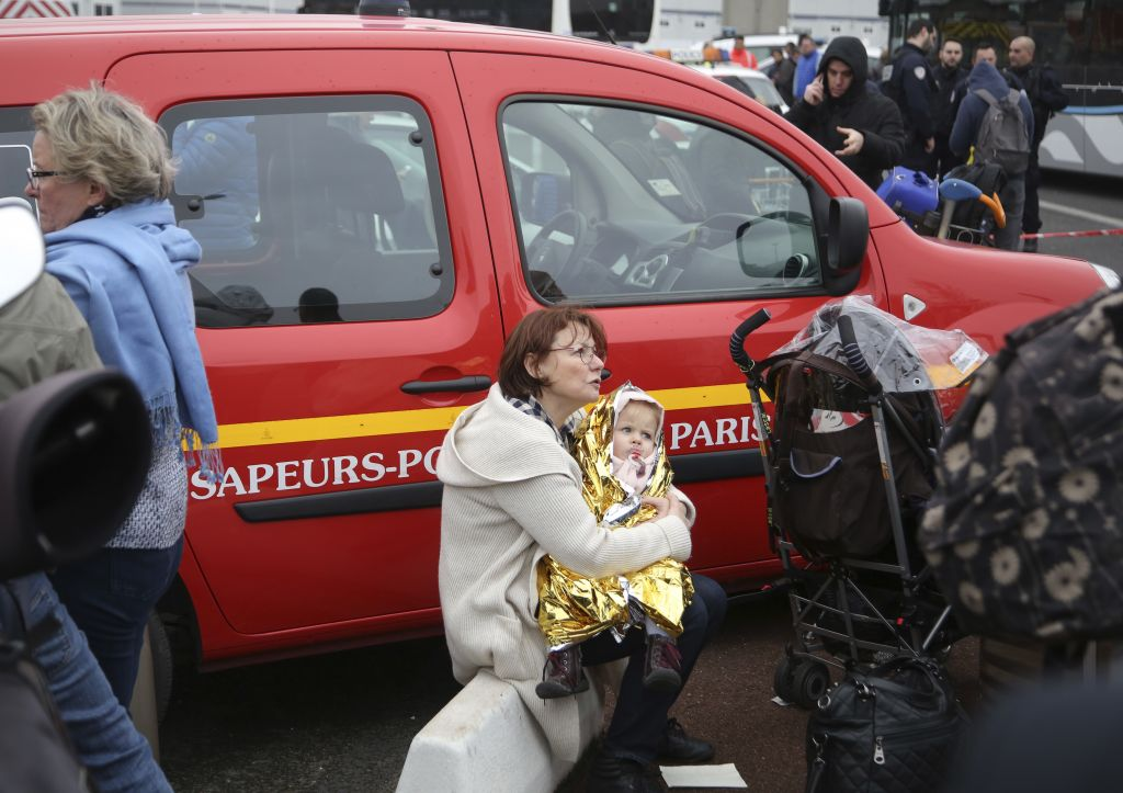 A woman holds a baby outside the Orly airport, south of Paris, Saturday, March, 18, 2017. A man was shot dead after wrestling a soldier to the ground at Paris' Orly Airport and trying to take her rifle, officials said. No one else in the busy terminal was hurt, but thousands of travelers were evacuated and flights were diverted to the city's other airport. (AP Photo/Thibault Camus)