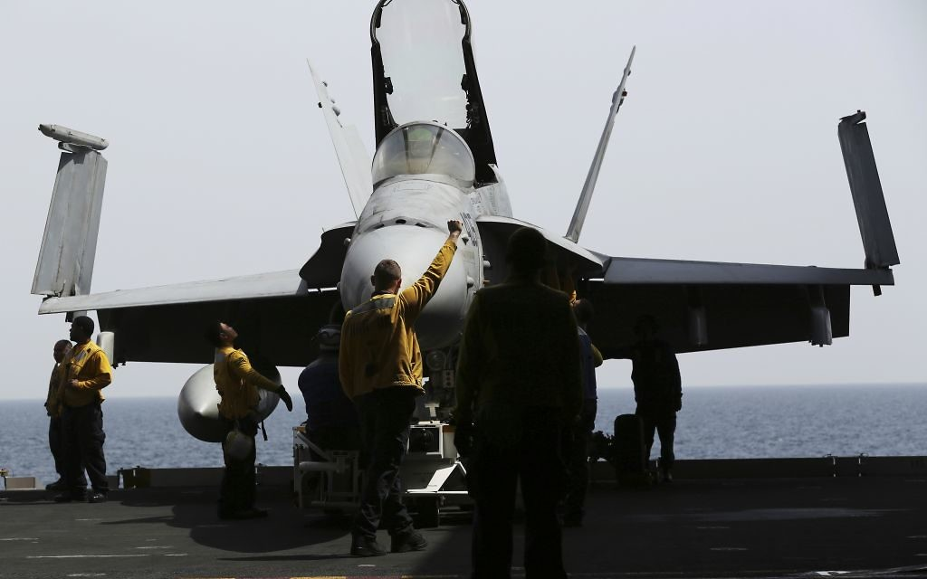 In this Wednesday, March 22, 2017 photograph, crew bring an F-18 below deck on the USS George H.W. Bush as it travels through the Persian Gulf. The carrier soon will begin launching airstrikes targeting the Islamic State group in Iraq and Syria. (AP Photo/Jon Gambrell)