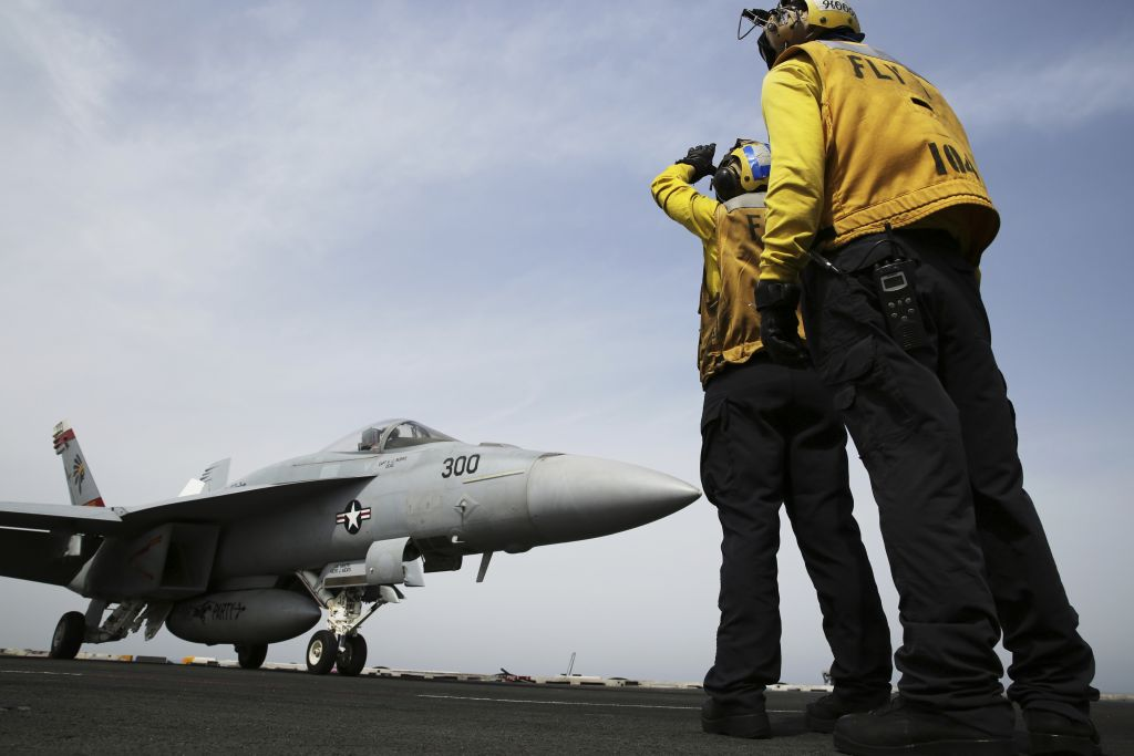 Illustrative: In this Wednesday, March 22, 2017 photograph, crew direct an F-18 on the USS George H.W. Bush as it travels through the Persian Gulf. (AP Photo/Jon Gambrell)