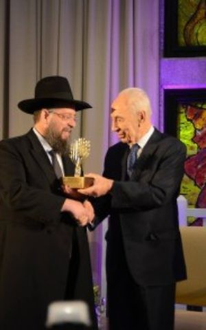 Rabbi Yeshayahu Heber receives an award from then-president Shimon Peres in 2014. (Matnat Chaim/Facebook)