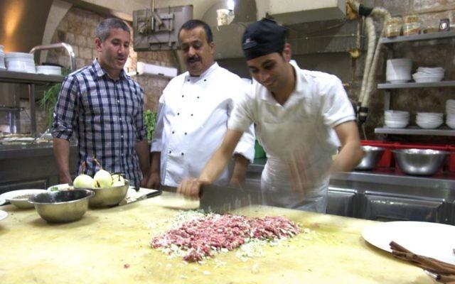 Chef Michael Solomonov (left) visits chef Husam Abbas (center) at his El Babor restaurant at Umm al-Fahm to learn how he makes his signature kebab El Babor dish. (Florentine Films)