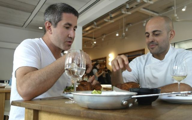 Chef Michael Solomonov (left) visits chef Meir Adoni at his Mizlala restaurant in Tel Aviv. They taste Adoni's kubaneh, Yemenite Shabbat bread. (Florentine Films)