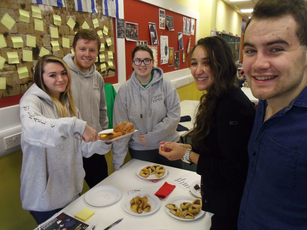 From left: Society members Louiza Vasiliu, Alan Lyne, Enya Harrison, Sara Epstein and Daniel McDowd at the food table. (Michael Riordan/Times of Israel)