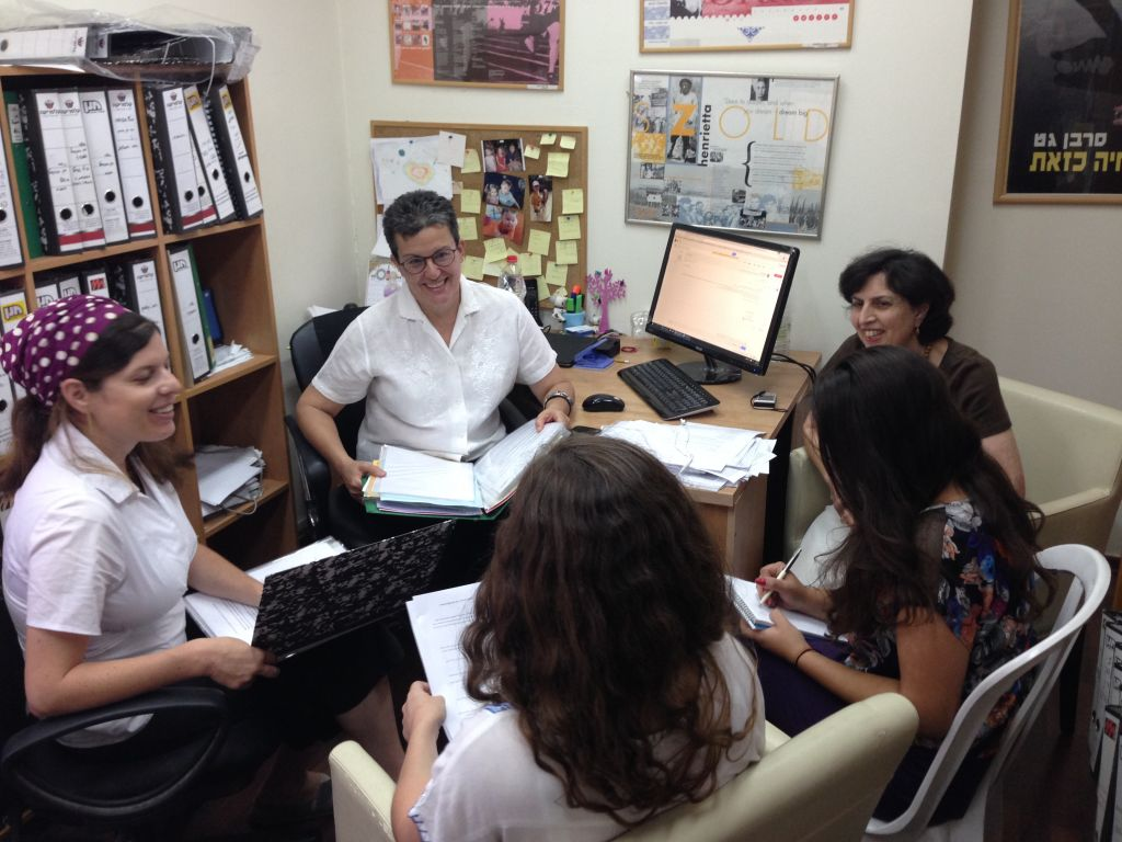 Dr. Susan Weiss, head of the Center for Women's Justice, sits with staff in its Jerusalem offices. (courtesy)