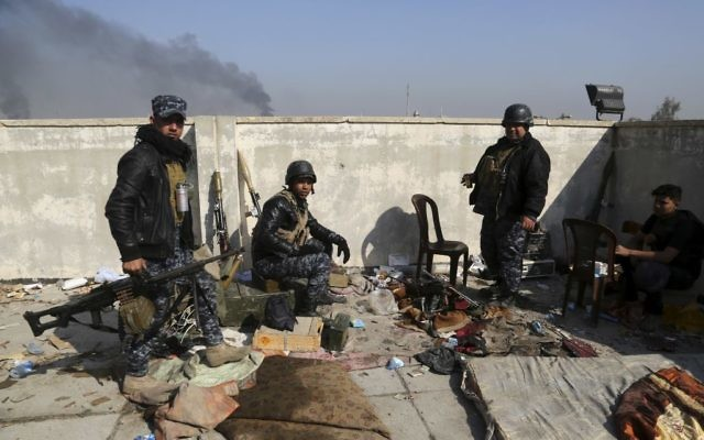 Soldiers take combat positions as Iraqi security forces advance during fighting against Islamic State militants in western Mosul, Iraq, Tuesday, March 7, 2017. (AP/Khalid Mohammed)