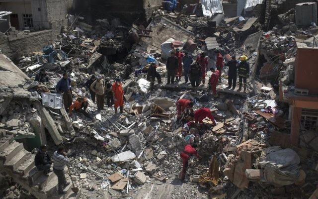 Civil protection rescue team work on the debris of a destroyed house to recover the body of people killed during fights between Iraq security forces and Islamic State on the western side of Mosul, Iraq, Friday, March 24, 2017. (AP Photo/Felipe Dana)