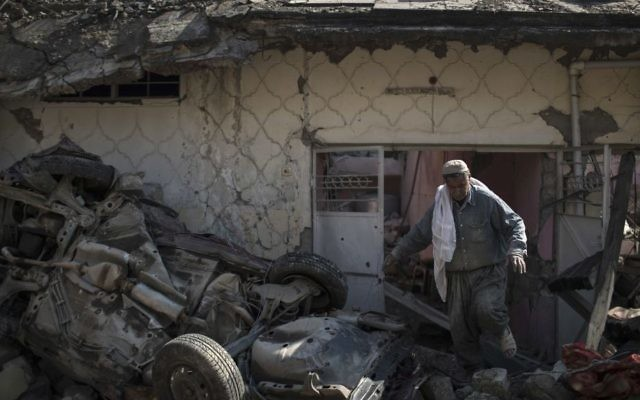 A man exits house damaged during fights between Iraq security forces and Islamic State on the western side of Mosul, Iraq, Friday, March 24, 2017.  (Felipe Dana/AP)