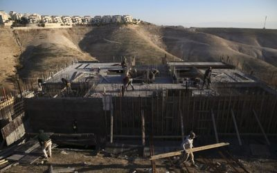 Palestinian laborers work at a construction site in a new housing project in the Israeli settlement of Maale Adumim, near Jerusalem,  February 7, 2017. (AP/Oded Balilty, File)