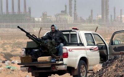 In this March 5, 2011 file photo, an anti-government rebel sits with an anti-aircraft weapon in front an oil refinery in Ras Lanouf, eastern Libya. (AP Photo/Hussein Malla, File)