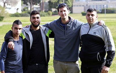 Anan Hujerat, left, Shadi Swaeed, center-left, and Mustafa Hujerat, right, participants of Israel's first army preparatory program geared towards Bedouin Israelis, pose with the head of the program, Tal Galin, center-right on their campus in Givat Haviva on February 27, 2017. (Judah Ari Gross/Times of Israel)