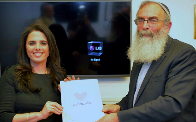 Justice Minister Ayalet Shaked with Tzohar founder Rabbi David Stav holding a new prenuptial agreement developed by the organization for Israeli Jewish couples to sign ahead of weddings. (Courtesy)