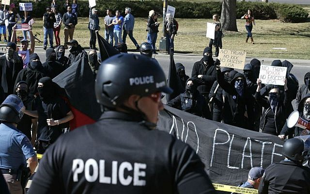 Anti-Trump protesters chant as police separate them from supporters of President Donald Trump gathered nearby during a March 4 Trump rally on the state Capitol steps in Denver, Colorado, Saturday, March 4, 2017. (AP Photo/Brennan Linsley)
