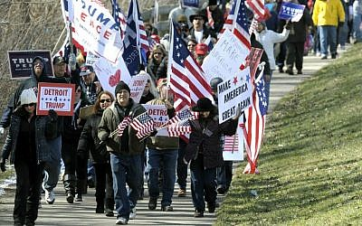 Trump supporters march east on the bike path along Metro Parkway in Clinton Township, Michigan, Saturday, March 4, 2017. (Todd McInturf/Detroit News via AP)