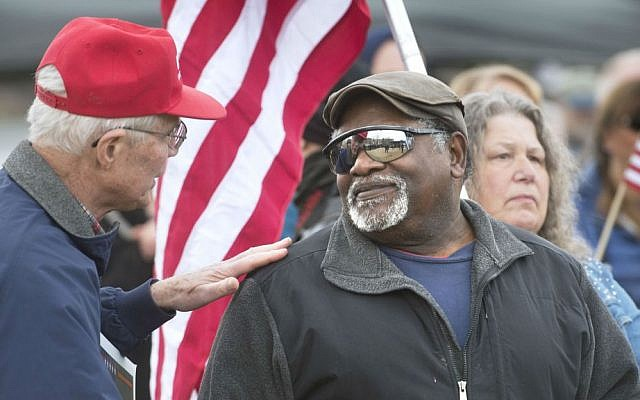 Robert Rigert, left, of Naselle, Washington, talks with Glenn Fowler of Belfair, Washington, during a rally for President Donald Trump at Heritage Park in Olympia, Washington, on Saturday, March 4, 2017. (Tony Overman/The Olympian via AP)