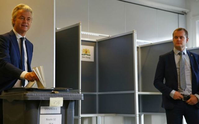 A security guard looks on as Geert Wilders, left, casts his ballot for the Dutch general election in The Hague, Netherlands, Wednesday, March 15, 2017. (AP Photo/Peter Dejong)