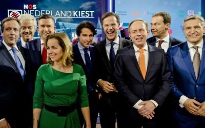 Democrats 66 party leader Alexander Pechtold, right-wing populist leader Geert Wilders, Socialist Party leader Emile Roemer, Party for the Animals' Marianne Thieme, Green Left party leader Jesse Klaver, Dutch Prime Minister Mark Rutte, Cornelis Gerrit (Kees) van der Staaij, Labour Party leader Lodewijk Asscher, and Christan Democrats party leader Sybrand Buma, from left, pose for a picture after the closing debate at parliament in The Hague, Netherlands, Tuesday, March 14, 2017. (Robin van Lonkhuijsen ANP POOL via AP)