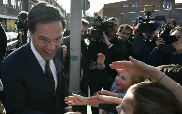Dutch Prime Minister Mark Rutte shakes hands with children after casting his vote for the Dutch general election in The Hague, Netherlands, Wednesday, March 15, 2017. (AP Photo/Patrick Post)