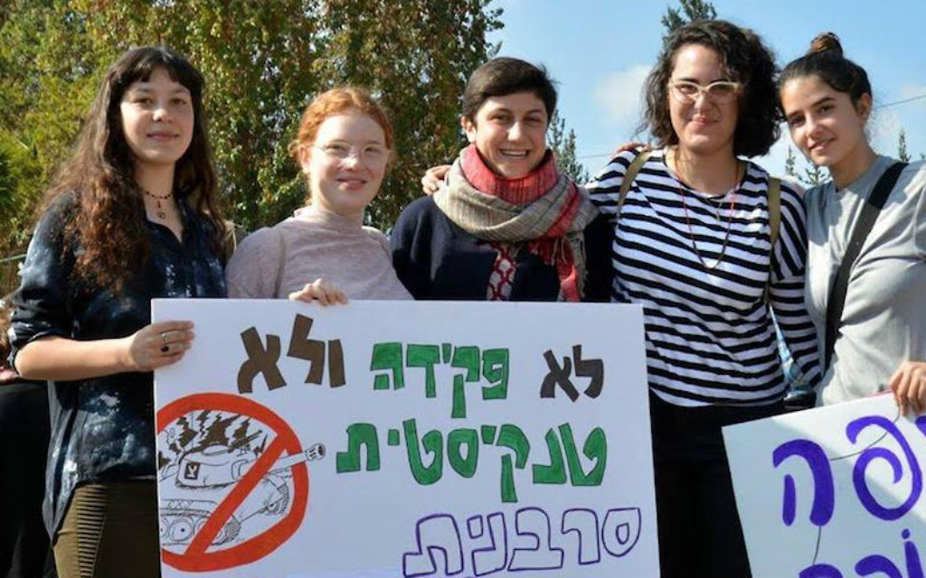Tamar Alon, second from left, and Tamar Ze'evi, center, protesting against being drafted into the Israeli army. The sign reads, 'Neither clerks nor tank drivers, we are refusers and feminists.' (Courtesy of Mesarvot)